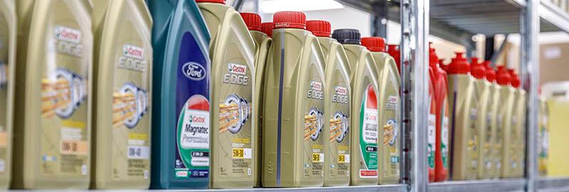 Een afbeelding van een schap bij Oliehandel Hettema met diverse jerry cans van merknamen, waaronder Ford en Castrol